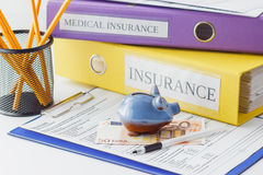 Clean insurance form, folders, pen and piggy bank. Soft focus background Stock Photography