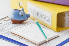 Clean insurance form, folders, pencil, notepad and piggy bank. Soft focus background Stock Photography