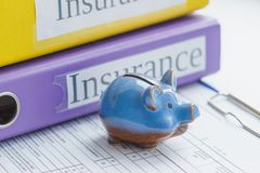 Clean insurance form, folders and piggy bank. Soft focus background Stock Images
