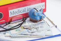 Clean insurance form, piggy bank, glasses and money. Soft focus background Stock Photos