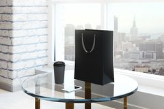 Clean interior with shopping bag. Empty shopping bag, coffee cup and smartphone placed on glass table in clean brick interior with city view and daylight. Mock Royalty Free Stock Photo