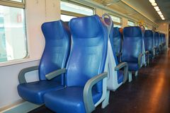 Clean Italian train, inside, Venice. Clean empty and blue chairs in a speedy Italian train, in Venice, Italy, Europe. Lights on Royalty Free Stock Photography