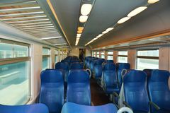 Clean Italian train, Venice. Clean blue chairs, beautiful windows, in a speedy Italian train, in Venice, Italy, Europe. Lights on, in the evening Stock Photography