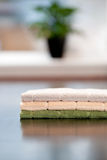 Clean Kitchen. Three clean kitchen cloths on a table with a window and plant out of focus in the background Stock Photos