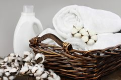 Clean Laundered Towels Soap and Cotton Flowers. Laundry basket filled white fluffy towels, cotton flowers and a bottle of liquid soap against a blurred grey stock image