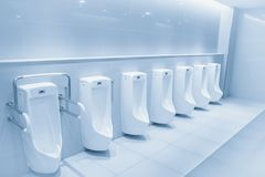 Clean male toilet row of urinals in restroom. Clean male toilet row of urinals in a public restroom Royalty Free Stock Photo