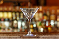 Clean martini glass. A clean martini glass stands on the blurred background of the bar counter, a traditional bar background Stock Photo