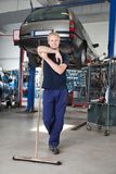 Clean Mechanic Garage. Full length portrait of young man leaning on broom in garage Royalty Free Stock Photo