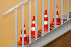 Clean new orange-white reflective road cones stand indoors. On a gray metal staircase against a background of beige wall Stock Photo