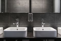 Clean new public toilet room empty. Two sinks and soap tank royalty free stock photos