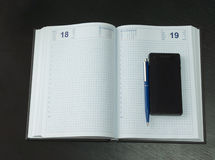 Clean Notebook with Pen and Phone. Close up Clean Open Memo Notebook with Blue Pen and Mobile Phone on Black Table Stock Photos