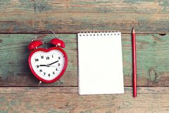 Clean notepad with heart-shaped alarm clock on old woooden backg Royalty Free Stock Photo