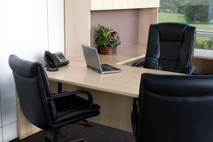 Clean office close up. Clean corner office with chairs, telephone and laptop. Close up view with bright windows in the background Royalty Free Stock Images