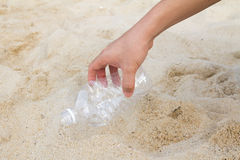 Clean our beach. Hand picking up a plastic bottle from beach, cleaning up the beach Royalty Free Stock Images