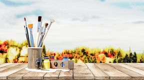 Clean paintbrushes with various color paints on a old wooden table with nature in background. Concept of painting in nature, 3d rendering stock photo
