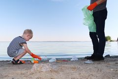 A small child collects trash on the beach. His dad points his finger where to throw garbage. Parents teach children cleanliness. Clean planet concept. A small royalty free stock images