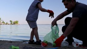 A small child collects trash on the beach. His dad points his finger where to throw garbage. Parents teach children cleanliness. Clean planet concept. A small stock footage