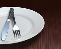 Clean plate & cutlery on dark woodgrain table Royalty Free Stock Photos