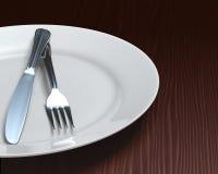 Clean plate & cutlery on dark woodgrain table. Casually set plate and cutlery on rich, dark woodgrain surface Royalty Free Stock Photos