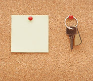 Clean post-it note. And home keys stuck to a cork notice board Stock Image