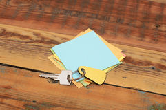 Clean post-it note. On a wood background with a key Stock Photography
