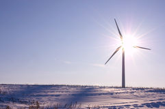 Clean Power. Wind turbine shot against the sun on the clear blue winter day. Concept picture for renewable energy; rule of thirds, closed aperture Royalty Free Stock Image