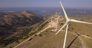 Clean power wind turbines; drone footage. Drone footage of wind turbines on mountain with sea in distance stock video footage