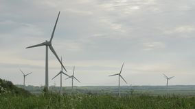 Clean and renewable energy, wind power, turbine, windmill, energy production. Wind turbines in the field, overcast. Clean and renewable energy, wind power stock footage