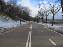 Clean road in winter park. Clean road, snow, winter park, blue sky, trees stock images