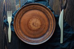 Clean rustic plate and forks on a wooden background royalty free stock photos