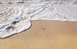 Clean sea sand on the beach with an incoming foamy wave. Top view stock photos