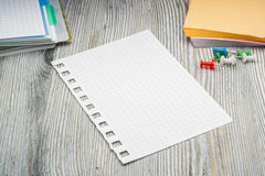 Clean sheet in cell from notebook on rustic table. Notes. Royalty Free Stock Photo