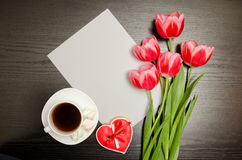 Clean sheet of paper, pink tulips and a mug of coffee. Black table. top view Stock Image