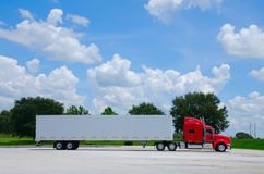 Clean shiny red semi tractor truck w cargo trailer. Clean shiny red long haul 16-wheel semi tractor truck with a clean white cargo container trailer against a Stock Image
