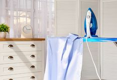Clean shirt and iron on board. Indoors stock photo