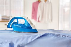 Clean shirt and iron on board. Indoors stock image
