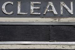Clean Sign. A weather beaten wooden CLEAN sign in a serif typeface stock photos