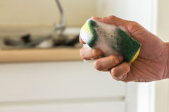 Clean sponge in hand and kitchenware background Stock Photos