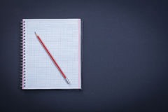 Clean squared workbook with red pencil on black Royalty Free Stock Photography