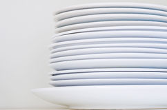 Clean stacked plates. Close-up of clean stacked plates in front of a neutral background Stock Image