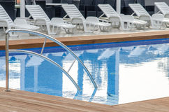 Clean swimming pool and empty resting chair Stock Image