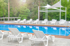 Clean swimming pool and empty resting chair Stock Photography