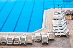 Clean swimming pool and empty resting chairs Stock Photography