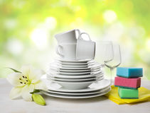 Clean tableware, dishwashing sponges and lily flower over abstract background Stock Image