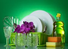 Clean tableware in rack, crystal wine glasses, detergent and sponges on green Royalty Free Stock Photos