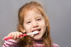 Clean teeth of pretty child. Girl brushing her teeth with toothbrush Stock Images