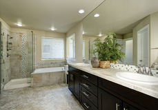 Clean and tidy bathroom interior. Long modern vanity cabinet with two sinks, bathtub with tile trim and shower. Northwest, USA Royalty Free Stock Images
