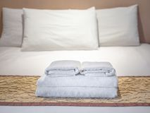 Clean towels on bed in hotel room stock image