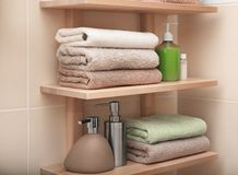 Clean towels and cosmetics on shelves. In bathroom Stock Photography