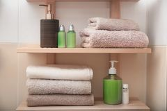 Clean towels and cosmetics on shelves. In bathroom Stock Image